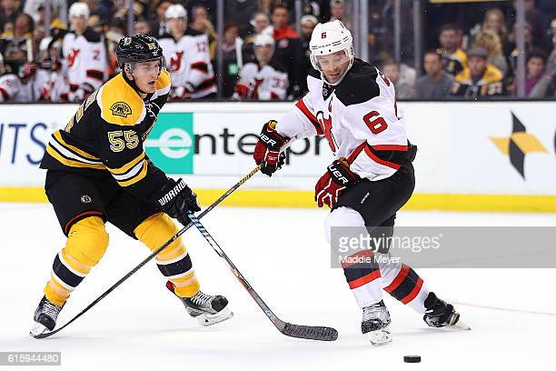Noel Acciari of the Boston Bruins and Andy Greene of the New Jersey Devils battle for control of the puck during the third period at TD Garden on...