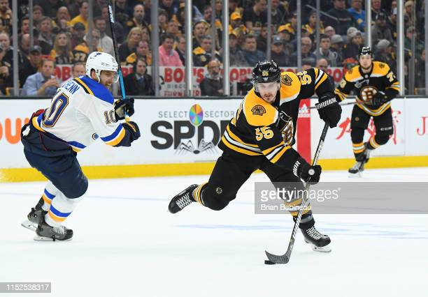 Noel Acciari of the Boston Bruins handles the puck against Brayden Schenn of the St Louis Blues during Game Two of the 2019 NHL Stanley Cup Final at...