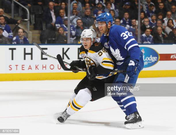 Noel Acciari of the Boston Bruins is checked by Josh Leivo of the Toronto Maple Leafs at the Air Canada Centre on November 10 2017 in Toronto Canada...