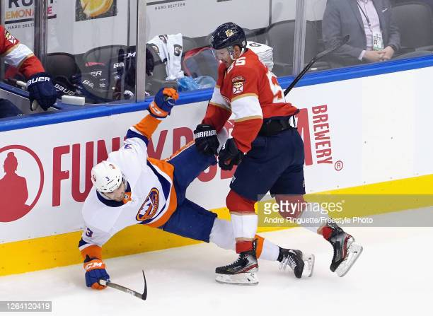 Noel Acciari of the Florida Panthers checks Adam Pelech of the New York Islanders during the first period in Game Three of the Eastern Conference...