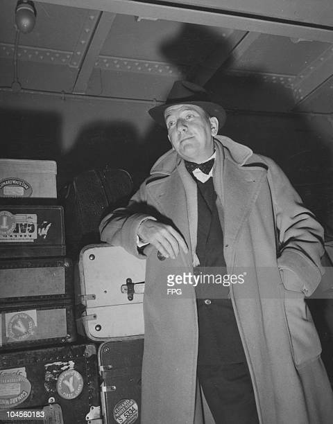 Noel Coward British playwright author and actor wearing an overcoat and hat while leaning against his luggage upon his arrival in New York City New...