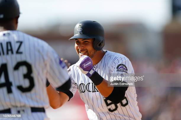 Noel Cuevas of the Colorado Rockies celebrates after his goahead two RBI single with first bast coach Tony Diaz during the eighth inning against the...