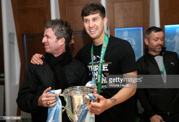 Noel Gallagher and John Stones of Manchester City pose with the trophy in the dressing room after the Carabao Cup Final between Aston Villa and...