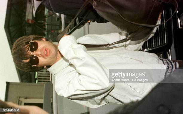 Noel Gallagher of the band Oasis loads his luggage into a waiting limousine after their arrival back at Gatwick Airport from Mexico after completing...