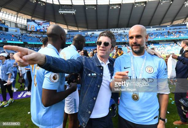 Noel Gallagher speaks to Josep Guardiola Manager of Manchester City on the pitch after the Premier League match between Manchester City and...