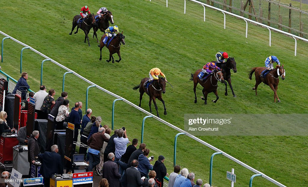 Noel Garbutt riding Purple Party (L, orange/yellow) win The Stramline Taxis - Official Transport Partner Handicap Stakes at Brighton racecourse on Septmber 05, 2016 in Brighton, England.