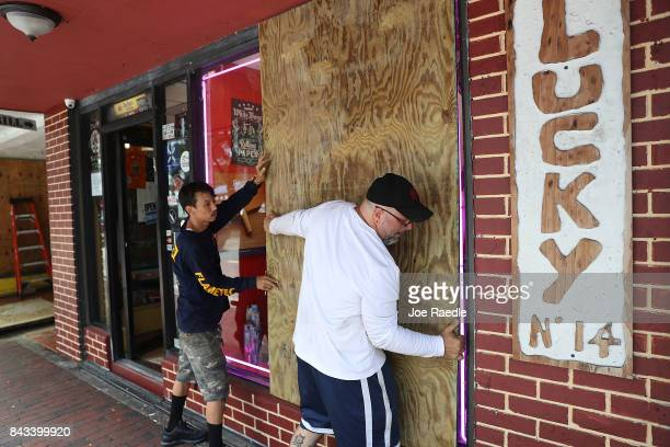 Noel Garcia and Mike Ehlis put plywood over windows of Noel's business as they prepare for Hurricane Irma on September 6 2017 in Miami Florida It's...