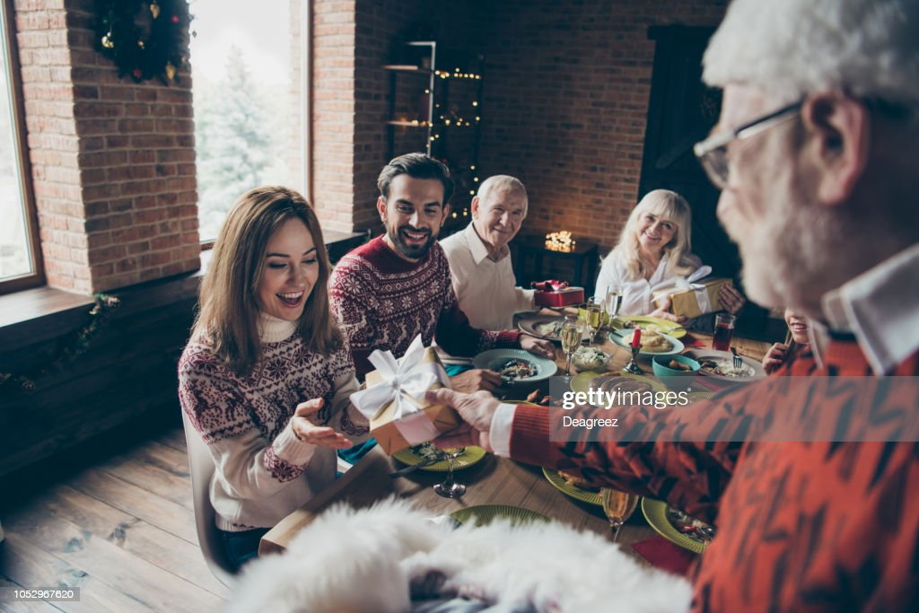 Noel morning family gathering. Nice adorable cheerful grey-haired grandparents, relatives, pre-teen sister, brother at house feast, sitting at lunch table, getting surprise presents fun joy : Stock Photo