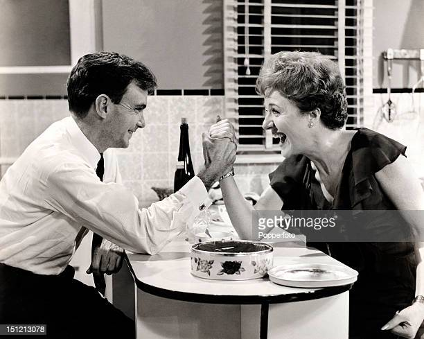Noele Gordon armwrestling with 'Crossroads' producer Reg Watson on the set of the soap opera at ATV Studios in Birmingham circa 1965