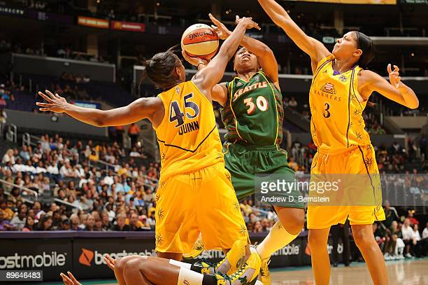 Noelle Quinn and Candace Parker of the Los Angeles Sparks block a shot from Tanisha Wright of the Seattle Storm at Staples Center August 6 2009 in...