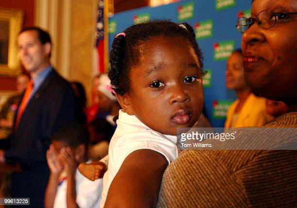 Noelle Tucker rests on the shoulder of her mother Tracy during a news conference with Sen Rick Santorum RPa and rchbishop of Washington Theodore...