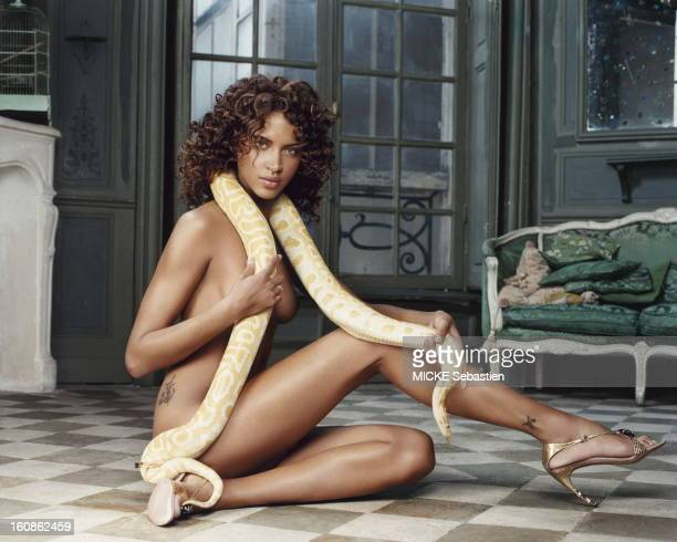Noemie Lenoir attitude of posing naked sitting on the ground a snake around his neck tattoos on the hip and ankle in an apartment of IIIrd district...