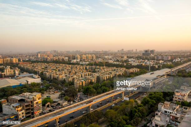 noida cityscape at dusk with the metro station, track and buildings - haryana stock pictures, royalty-free photos & images
