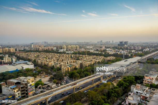 noida cityscape at dusk with the metro station, track and buildings - delhi stock pictures, royalty-free photos & images