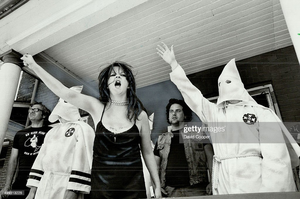 Members of the Ku Klux Klan; on the verandah of a Dundas St. E. house in May; raise arms in Nazi-style salute and shout at marchers from Riverdale Action Committee Against Racism who were protesting the Klan's activities. The committee had been infiltrated by the chief of the klan's intelligence agency (KIA). Insight