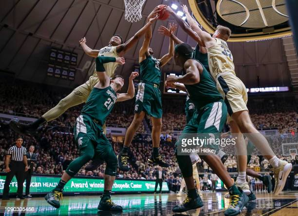 Nojel Eastern and Matt Haarms of the Purdue Boilermakers reach for a rebound against Kenny Goins of the Michigan State Spartans at Mackey Arena on...