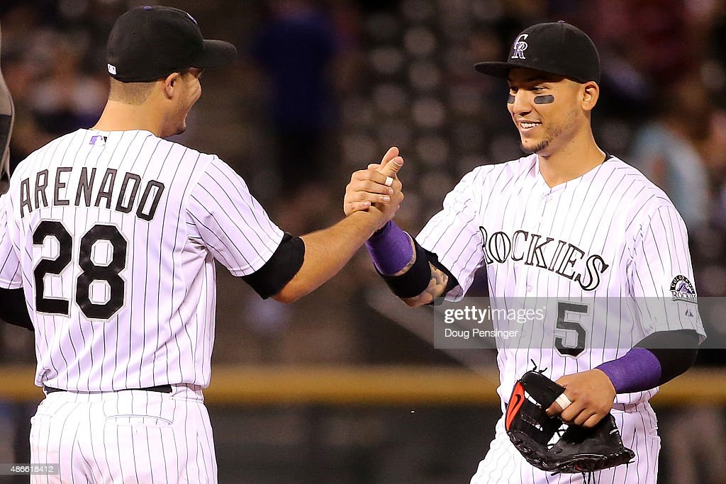 Nolan Arenado #28 and Carlos Gonzalez #5 of the Colorado Rockies celebrate their victory over the San Francisco Giants at Coors Field on September 4, 2015 in Denver, Colorado. Arenado and Gonzalez had back to back solo home runs off of Chris Heston #53 of the San Francisco Giants in the first inning as the Rockies defeated the Giants 2-1.