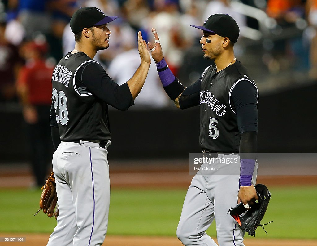 Nolan Arenado #28 and Carlos Gonzalez #5 of the Colorado Rockies congratulate each other after defeating the New York Mets 6-1 in a game at Citi Field on July 29, 2016 in the Flushing neighborhood of the Queens borough of New York City.