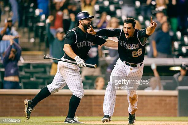 Nolan Arenado and Michael McKenry of the Colorado Rockies celebrate after Arenado scored the game winning run in the 13th inning against the Miami...