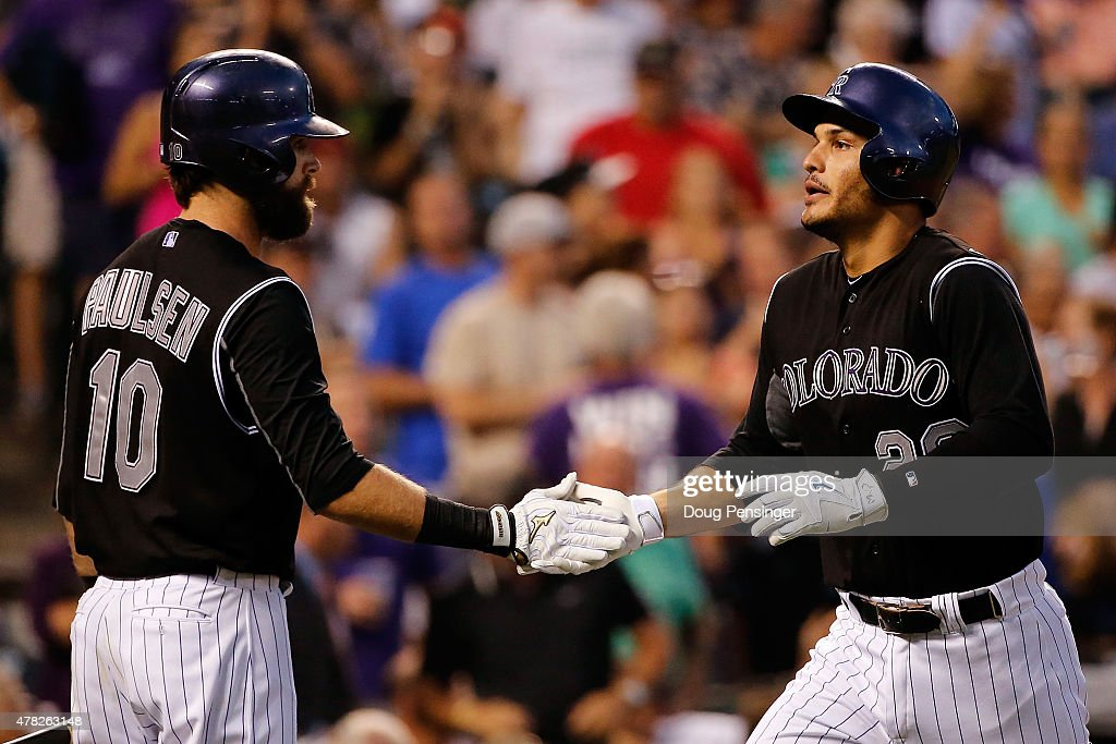 Nolan Arenado #28 of the Colorado Rockies celebrates his solo home run off of Chase Anderson #57 of the Arizona Diamondbacks with Ben Paulsen #10 of the Colorado Rockies as the Diamondbacks held a 3-2 lead in the fourth inning at Coors Field on June 23, 2015 in Denver, Colorado.