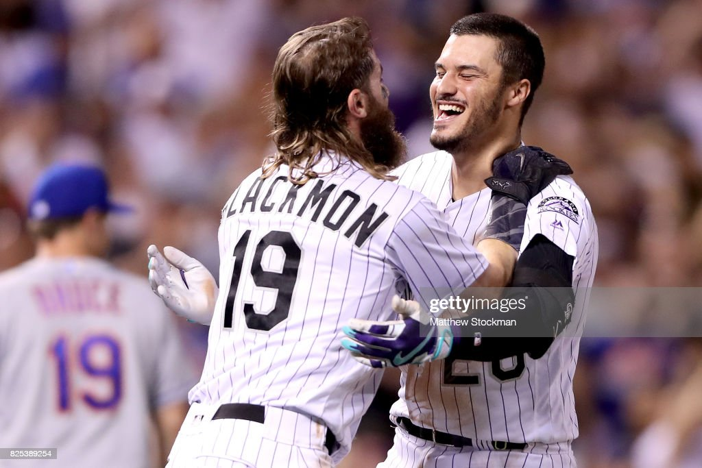 Nolan Arenado #28 of the Colorado Rockies celebrates with Charlie Blackmon #19 after driving in the game winning run in the ninth inning against the New York Mets at Coors Field on August 1, 2017 in Denver, Colorado.