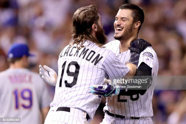 Nolan Arenado of the Colorado Rockies celebrates with Charlie Blackmon after driving in the game winning run in the ninth inning against the New York...