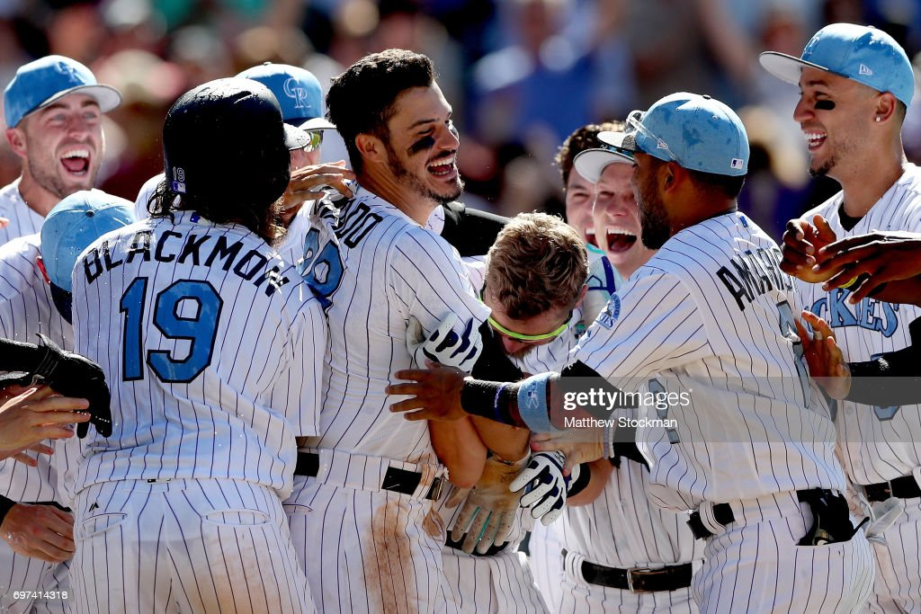 Nolan Arenado #28 of the Colorado Rockies celebrates with his teammates after hitting a 3 RBI walk off home run in the ninth inning against the San Francisco Giants at Coors Field on June 18, 2017 in Denver, Colorado.