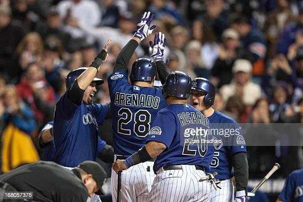 Nolan Arenado of the Colorado Rockies celebrates with Michael Cuddyer Wilin Rosario and Wilin Rosario after hitting a grand slam home run in the...