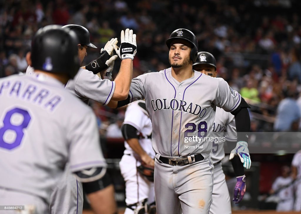 Nolan Arenado #28 of the Colorado Rockies celebrates with teammates DJ LeMahieu #9 and Gerardo Parra #8 after hitting a three run home run off of Jake Barrett #33 of the Arizona Diamondbacks during the eighth inning at Chase Field on September 11, 2017 in Phoenix, Arizona.