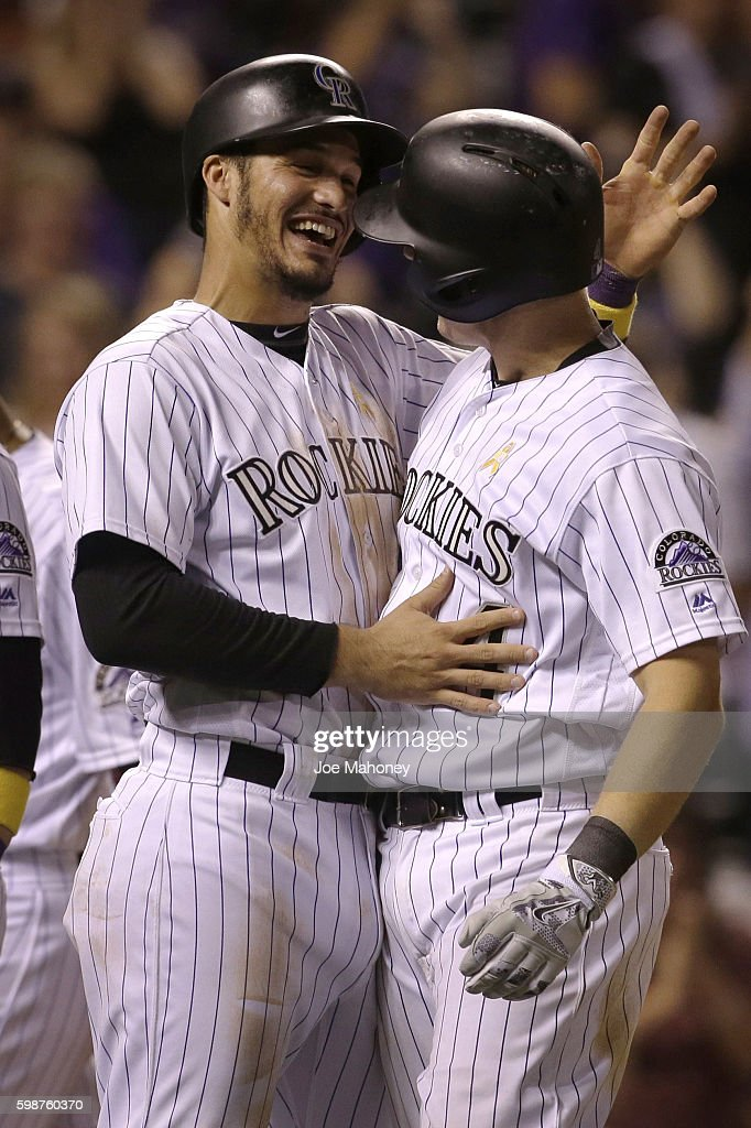 Nolan Arenado #28 of the Colorado Rockies congratulates Nick Hundley #4 of the Colorado Rockies after his grand slam home run in the eighth inning of a baseball game against the Arizona Diamondbacks at Coors Field on September 2, 2016 in Denver, Colorado. The Rockies won 14-7.