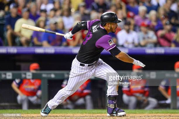 Nolan Arenado of the Colorado Rockies hits an eighth inning RBI double against the St Louis Cardinals at Coors Field on August 25 2018 in Denver...