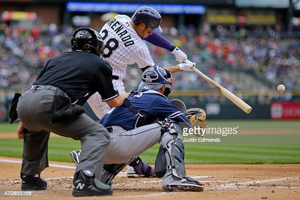 Nolan Arenado of the Colorado Rockies hits an infield single during the first inning as catcher Wil Nieves of the San Diego Padres and home plate...
