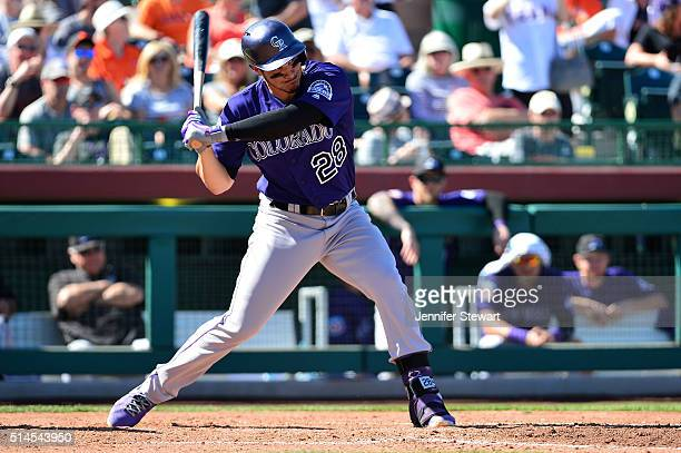 Nolan Arenado of the Colorado Rockies hits an RBI single in the fifth inning against the San Francisco Giants in the spring training game at...
