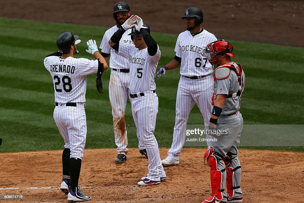 Nolan Arenado #28 of the Colorado Rockies is congratulated at home plate after hitting a grand slam by Carlos Gonzalez #5, Charlie Blackmon #19 and German Marquez #67 as catcher Carson Kelly #71 of the St. Louis Cardinals looks on during the second inning at Coors Field on September 21, 2016 in Denver, Colorado.