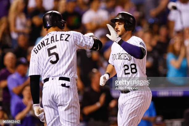 Nolan Arenado of the Colorado Rockies is congratulated by Carlos Gonzalez after hitting a solo home run during the seventh inning against the Los...