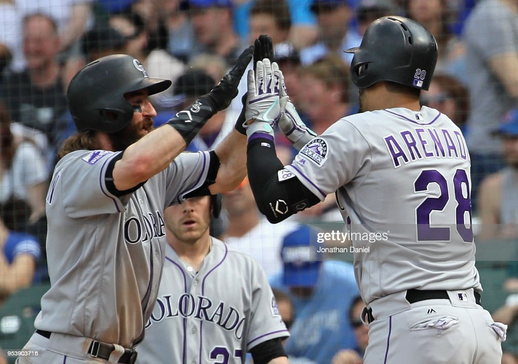 Nolan Arenado #28 of the Colorado Rockies is congratulated by Charlie Blackmon #19 after hitting his second home run of the game, a three run shot in the 8th inning, against the Chicago Cubs at Wrigley Field on May 2, 2018 in Chicago, Illinois.