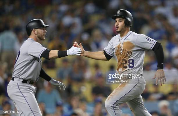Nolan Arenado of the Colorado Rockies is greeted by Trevor Story in the ninth inning after Arenado scored the Rockies' sixth run against the Los...