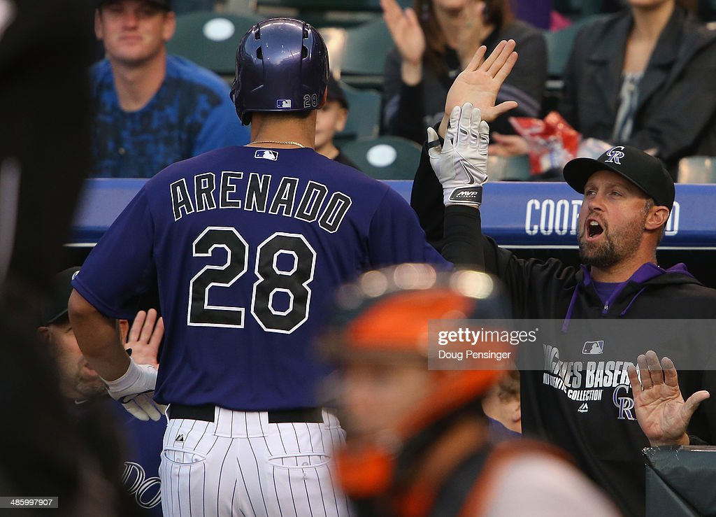 Nolan Arenado #28 of the Colorado Rockies is welcomed back to the dugout by Michael Cuddyer #3 of the Colorado Rockies after his solo home run off of starting pitcher Ryan Vogelsong #32 of the San Francisco Giants to take a 1-0 lead in the first inning at Coors Field on April 21, 2014 in Denver, Colorado. The Rockies defeated the Giants 8-2.