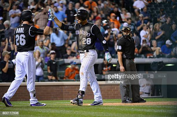 Nolan Arenado of the Colorado Rockies its a solo shot home run and is congratulated by team mate David Dahl d against the San Francisco Giants at...