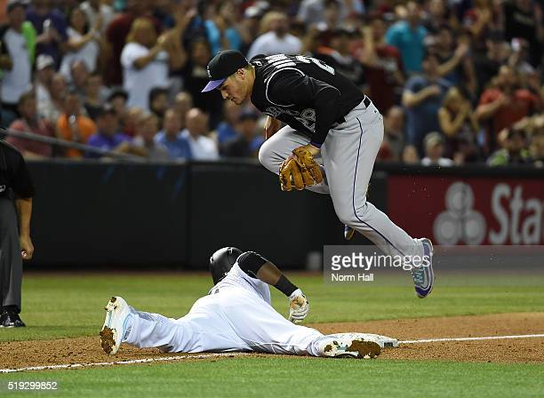 Nolan Arenado of the Colorado Rockies jumps over the top of Rickie Weeks Jr of the Arizona Diamondbacks who safely dove back into third base during...