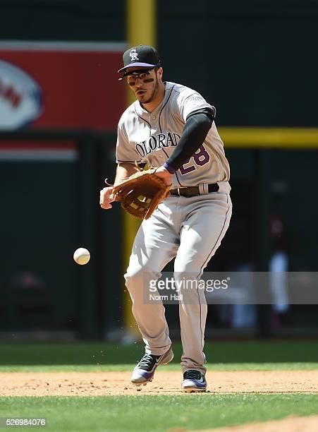 Nolan Arenado of the Colorado Rockies makes a play on a bouncing ball off the bat of Yasmany Tomas of the Arizona Diamondbacks who was thrown out at...