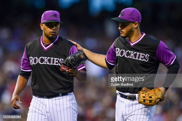 Nolan Arenado of the Colorado Rockies pats German Marquez on the back after a sharp ground ball took Marquez' glove off his hand on an inning ending...