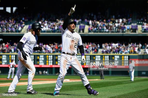 Nolan Arenado of the Colorado Rockies points to the crowd and is congratulated by Charlie Blackmon after hitting a first inning tworun homerun...