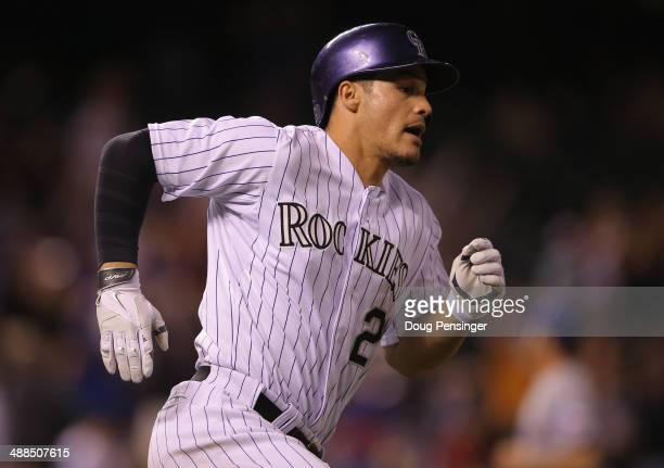Nolan Arenado of the Colorado Rockies rounds the bases on an RBI double off of Neal Cotts of the Texas Rangers to score Carlos Gonzalez of the...