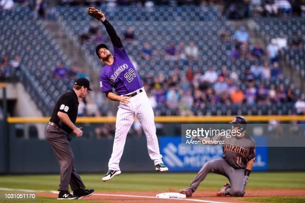 Nolan Arenado of the Colorado Rockies saves a high throw from the outfield as AJ Pollock of the Arizona Diamondbacks slides into third base safely...