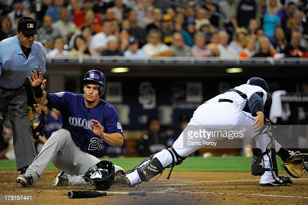 Nolan Arenado of the Colorado Rockies scores ahead of the tag of Rene Rivera of the San Diego Padres during the sixth inning of a baseball game at...