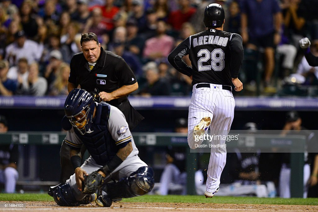 Nolan Arenado #28 of the Colorado Rockies scores in the third inning of a game as Martin Maldonado #12 of the Milwaukee Brewers handles the throw to the plate at Coors Field on September 30, 2016 in Denver, Colorado.
