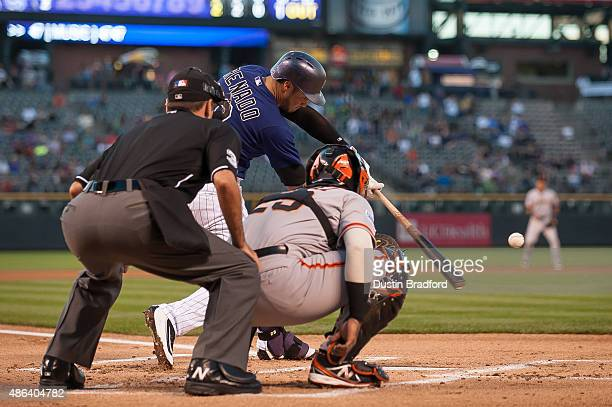 Nolan Arenado of the Colorado Rockies singles in front of Hector Sanchez of the San Francisco Giants and umpire Pat Hoberg in the first inning of a...