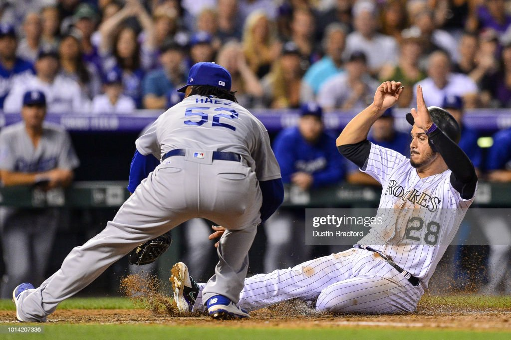Nolan Arenado #28 of the Colorado Rockies slides home to score from third base on a passed ball as Pedro Baez #52 of the Los Angeles Dodgers attempts a tag in the seventh inning of a game at Coors Field on August 9, 2018 in Denver, Colorado.