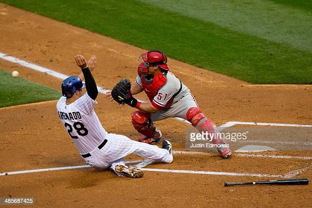 Nolan Arenado of the Colorado Rockies slides in to score as catcher Carlos Ruiz of the Philadelphia Phillies receives the throw during the third...